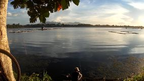 Man use fishing rod to catch fish on a lake at sunset. San Pablo Cityy, Laguna, Philippines - August 2, 2015: Man use fishing rod to catch fish on a lake at stock footage