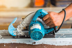 Man use handheld powerful circular saw in construction site. royalty free stock image