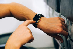 Man use his smart watch in aircraft. Man touch his smart watch on hand in aircraft Royalty Free Stock Photography