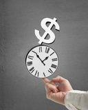 Man use index finger to balacne stacked clock and money in concr. Ete background Royalty Free Stock Images