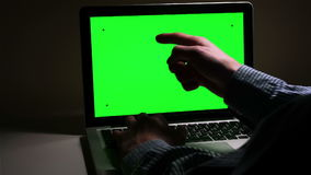 A man use a laptop on his desktop. A man use a laptop on his desktop with various hand gestures (scrolling, touching,typing) .Indoor.Green screen stock video footage