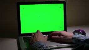 A man use a laptop on his desktop. A man use a laptop on his desktop with various hand gestures (scrolling, touching,typing) .Indoor.Green screen stock video