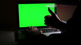 A man use a laptop on his desktop. A man use a laptop on his desktop with various hand gestures (scrolling, touching,typing) .Indoor.Green screen stock footage