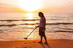 Man use metal detector. Man silhouette with metal detector on sunset on the beach royalty free stock photography