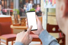 Man use mobile phone with isolated screen for mockup in coffee shop. Modern smart phone with round edges royalty free stock image