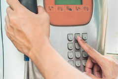 Man use Public phone pressing numpad number 2 Royalty Free Stock Images