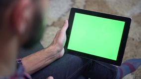 Man Use Tablet PC with Green Screen. A back shot of a lumbersexual man using tablet pc with green screen with slide gestures sitting on sofa stock footage
