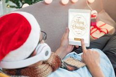 Man use tablet sending merry chirstms and new year gift card to. Friend online.winter holiday at home celebration,mobile digital lifestyle,relax on sofa and Stock Photography