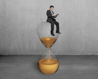 Man use tablet and sit on hourglass stock photography
