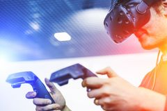 Man use virtual reality goggles or VR headset or helmet, play video game with wireless controllers, future is now concept. Man use virtual reality goggles or VR Stock Images