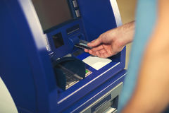 Man uses an ATM card inserted into the ATM machine. For cash Royalty Free Stock Photos