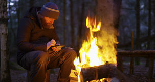 Man uses compass and smart phone by camp fire Royalty Free Stock Photography