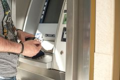 Man Uses a credit card at an ATM on the street. Operation with money. Modern payment technologies. Copy space.  Royalty Free Stock Photography