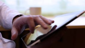Man uses digital tablet. Close-up man`s hands typing on the tablet stock footage