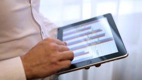 Man uses digital tablet. Man with digital tablet near the window stock footage