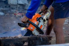 Man uses gasoline engine portable chainsaw cut timber into pieces stock photography