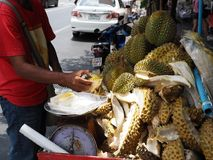 A man uses a knife to cut a durian fruit. BANGKOK, THAILAND - MAY 6, 2018: A man cuts durian fruits on a mobile food cart on May 6, 2018 in Thai capital Bangkok Stock Image