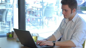 Man uses laptop at the cafe. Brunette man using laptop at the cafe. Young man sitting at the table with laptop and cup of tea. Caucasian man dressed in white stock video footage