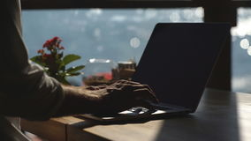 A man uses a laptop in a cafe on the waterfront stock video