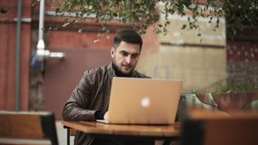 A man uses a laptop outdoor. Footage with slider stock video