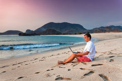 Man uses laptop remotely. At the beach royalty free stock photography