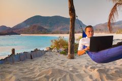 Man uses laptop remotely. At the beach royalty free stock images