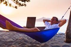 Man uses laptop remotely. Man lying on a hammock uses laptop remotely at the beach royalty free stock photos