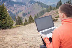 Man uses laptop remotely at mountain. Man dressed in red sweater uses laptop remotely with 3g or 4g network wireless at mountain royalty free stock photo