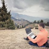 Man uses laptop remotely at mountain Royalty Free Stock Image