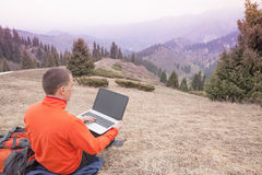 Man uses laptop remotely at mountain. Man dressed in red sweater uses laptop remotely with 3g or 4g network wireless at mountain, square orientation stock image