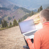 Man uses laptop remotely at mountain Stock Images