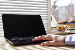 Man uses laptop on workplace. Royalty Free Stock Photo
