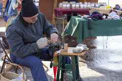 Man uses machine to make wool socks at an open air market. Royalty Free Stock Image
