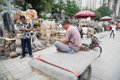 Man uses a mobile while the  Panjiayuan Antique Market, Beijing Stock Photos