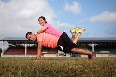 A man uses an orange shirt in a push-up position while the female partner who uses a pink shirt is on it. They exercise on the royalty free stock images