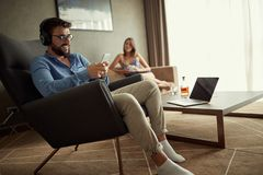 Man uses a phone with headphones to listen to music and relax at home royalty free stock photos
