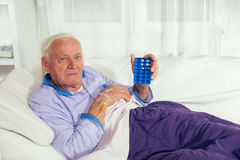 Man uses a pill organizer to prepare his medication for the week. Royalty Free Stock Image