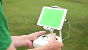 Man uses rc controller for UAV drone outside green screen tablet. A man uses a RC controller for a drone or UAV outside in an open field. Green screen generic stock video