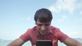 Happy successful man uses smart phone sitting near the tropical beach. slow motion. 1920x1080. Man uses smart phone standing near the tropical beach. slow motion stock video