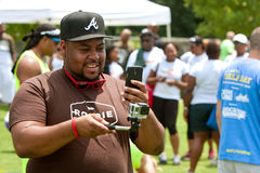 Man Uses Smart Phone To Operate GoPro Camera At Event. Atlanta, GA, USA - July 11, 2015:  A man operates a GoPro camera on a selfie stick by using his smart Stock Photo