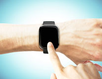 Man uses a smart watch on a blue background Stock Images