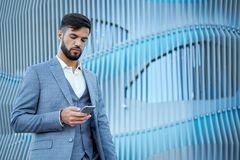 Man uses a smartphone. Businessman urban professional business man using mobile phone. Happy professional wearing suit jacket. Man uses a smartphone royalty free stock images