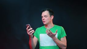 A man uses a smartphone at a nightclub party.