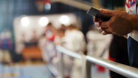 Man uses smartphone at sport competitions of karate Stock Photography