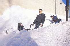 Man uses snow blower to clear snow from sidewalk in New Jersey near New York City after winter snowstorm Royalty Free Stock Image