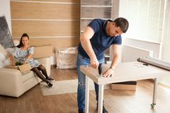 Man uses tools to assembly furniture in new house. He will use this furniture for the interior of the new flat royalty free stock image
