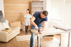 Man uses tools to assembly furniture in new house. He will use this furniture for the interior of the new flat royalty free stock photo