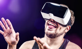 Man uses Virtual Realitiy VR head-mounted display. Man has fun using his Virtual Realitiy VR glasses head mounted display Royalty Free Stock Images