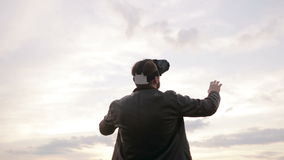 Man uses a virtual reality glasses against the sky