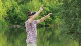 Man uses a virtual reality helmet outdoors. Bank of the river, summer day in nature. Technology in outdoors.  stock footage